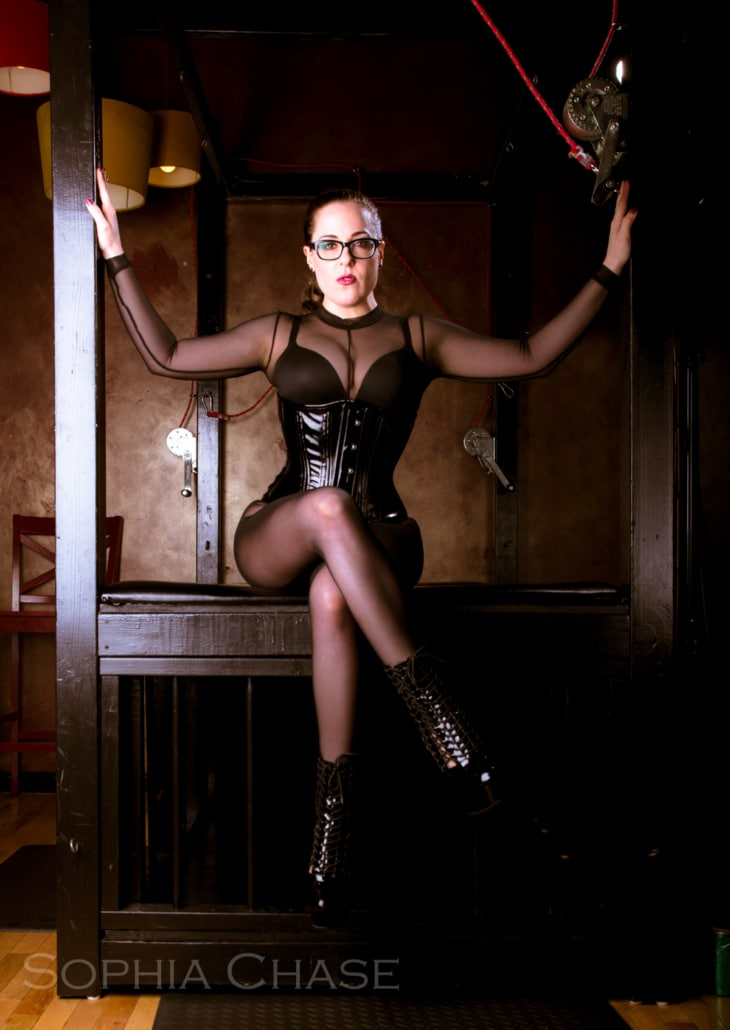 Chicago Dominatrix Lady Sophia Chase seated on a bondage table, legs crossed wearing a black mesh cat suit and corset